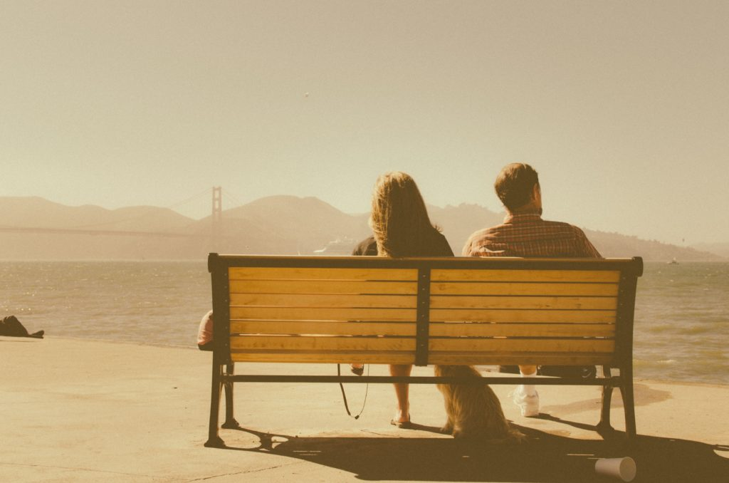couple sitting on a bench not talking