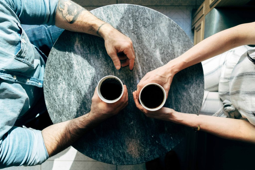two people at a table drinking coffee in conversation