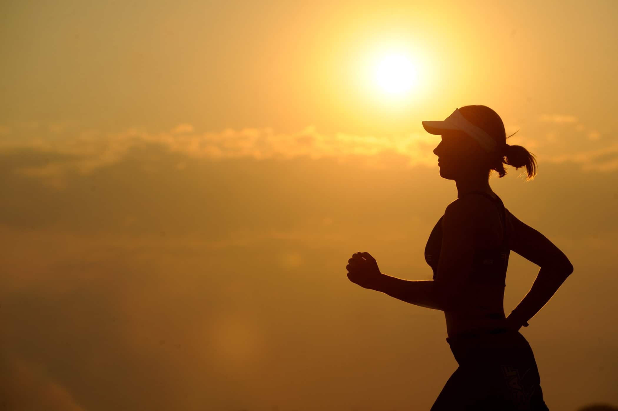 silhouette of woman running for exercise at sunset